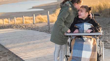 Girl in wheelchair at beach