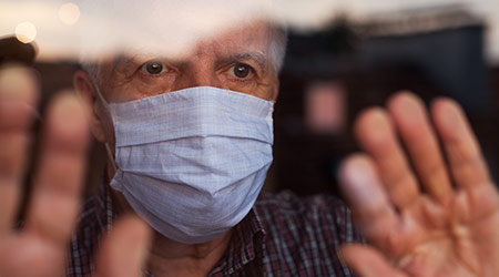 elderly man with mask next to window