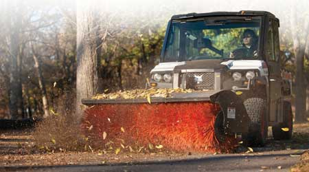Utility vehicle sweeping leaves